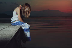 Lone woman in sad position over lake waters Stock Photo