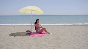 Lone woman sitting on beach under umbrella. Lone woman sitting on pink beach blanket under yellow umbrella with ocean at horizon stock video footage