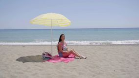 Lone woman sitting on beach under umbrella. Lone woman sitting on pink beach blanket under yellow umbrella with ocean at horizon stock footage