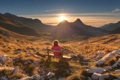 Woman on bench looking out at view of the mountain landscape Stock Image