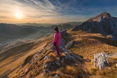 Woman hiker standing on the mountain cliff towards the setting s stock images
