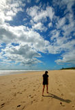 Lone woman walking at the beac. Woman having a slow walk at the beach stock images