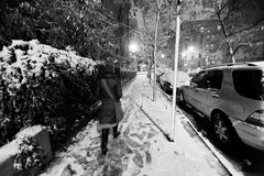 Lone woman walking on the snow covered pavement of a Harlem stre. Et on a freezing snowstorm night Stock Photo