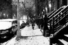 Anonymous Woman in Snow Storm at Harlem Manhattan New-York. Lone woman walking on the snow covered pavement of a Harlem street on a freezing snowstorm night Stock Photography