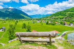 A lone wooden bench stands on top. Of a mountain Royalty Free Stock Photography