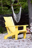 Lone yellow adirondack chair. A lone yellow Adirondack chair on a stone beach, with a hammock in the background Stock Photo