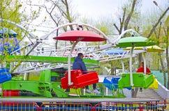 loneliness Único homem e única mulher em um carrossel em um parque da cidade Não poderão alcançar um com o otro imagens de stock