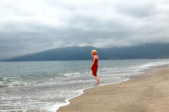 Loneliness. Red dressed caucasian women walking at a beach Royalty Free Stock Photography
