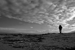Loneliness. Clouds over mediterranean sea with a dark figure of a person walking on the beach Royalty Free Stock Photos