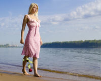 Loneliness. Sad girl walks along shore with rose in hand Stock Image