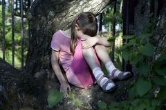 Loneliness. Little crying girl ten years old sitting on tree Royalty Free Stock Photo