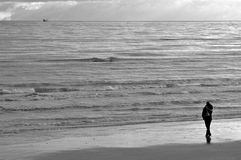 Loneliness. Black and white with woman standing in front of ocean Royalty Free Stock Photography
