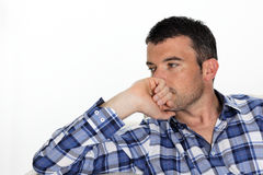 Loneliness. Pensive man with blue shirt at home Stock Image