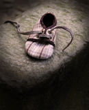 Loneliness. Small shoe lonely on stone Royalty Free Stock Images
