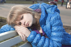 Loneliness. The sad blonde sits on a bench Stock Photos