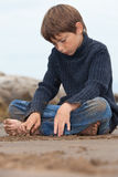 Loneliness. Lonely little boy at the beach Stock Photo