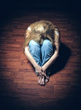 Loneliness. Sad woman sitting alone in a empty room Stock Images