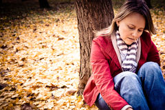 Loneliness. A young lonely woman sitting under a tree Stock Photo