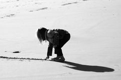 Loneliness. A photograph in black and white of caucasian longhaired lonely little girl playing with the sand on the beach outdoors. Her own big shadow is behind Stock Photos