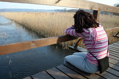Loneliness. Girl waiting on a wooden bridge with copyspace on the left Royalty Free Stock Photo