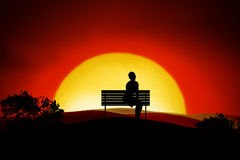 Loneliness. A person sitting alone on a bench in the sunset Royalty Free Stock Photos