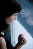 Loneliness. Lonely, sad young woman by the window with rain drops Stock Image