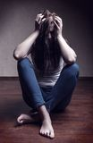 Loneliness. Addict girl sitting on the floor alone Stock Photo