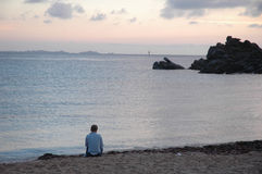 Loneliness on the beach. Loneliness of a woman on the beach during sunset Royalty Free Stock Images