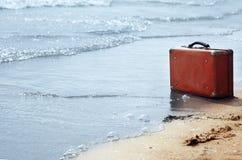 Loneliness on the beach. Lost orange handbag on the beach Stock Photos