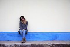Loneliness. Beautiful young girl sitting against yellow wall Stock Image
