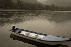 Loneliness. A boat resting on a rainy and cold summer day Stock Photo