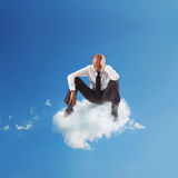 Loneliness businessman. Alone desperate businessman sitting on a cloud in the sky Royalty Free Stock Photography