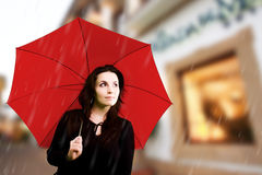 Loneliness in a city. Beautiful young woman with red umbrella on rainy day Royalty Free Stock Photo