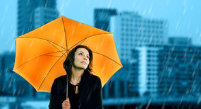 Loneliness in a city. Beautiful young woman with orange umbrella on rainy day Stock Images