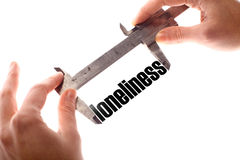Loneliness. Color horizontal shot of two hands holding a caliper and measuring the word loneliness Stock Images