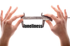 Loneliness. Color horizontal shot of two hands holding a caliper and measuring the word loneliness Stock Photos