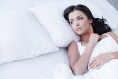 Loneliness. Depressed young woman lying on the bed and looking on empty pillow Stock Photos