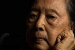 Loneliness elder woman crying. Loneliness Asian elder woman crying on black backgroundg Stock Images