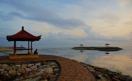 Loneliness. Encountering dawn alone on the ocean shore on the island of Bali Royalty Free Stock Photo