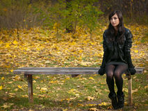 Loneliness in a fall. Alone young girl sits on a bench in autumn park Royalty Free Stock Images