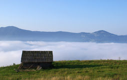 Loneliness in a fog. Wooden small house against mountains in a fog Stock Image