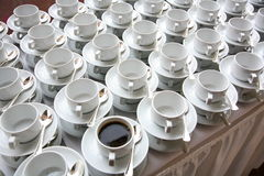 Loneliness (Individual and Society). Photo of white coffee cups with saucers and spoons. In one of the cups poured black coffee Stock Images