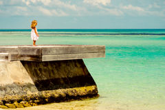 Loneliness little girl looking at the ocean Royalty Free Stock Photo