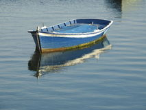 Loneliness. A lonely blue boat on the sea Stock Photos