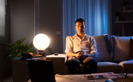 Loneliness. Lonely businessman at home sitting on sofa with hands clasped late at night Royalty Free Stock Photography
