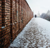 Loneliness. Man is  walking along the wall Royalty Free Stock Images