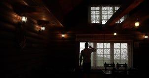 Loneliness. Man walks towards a window in a dark house watching how rain falls outside.  stock video footage