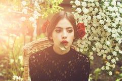 loneliness Menina bonito com a flor branca na boca na cara pensativa foto de stock royalty free