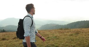 Loneliness in the mountains. Handsome young man with a backpack walks along the mountain road under heavy grey sky.  stock footage