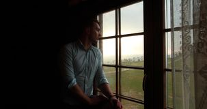 Loneliness in the mountains. Handsome young man looks sad standing before a window and watching epic sunset over the. Hills stock video